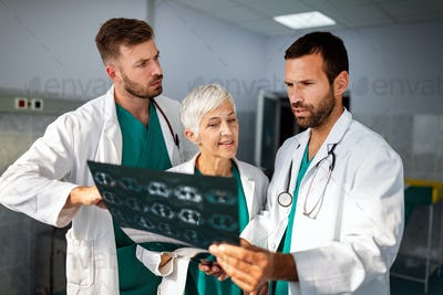 Doctors examining an x-ray report in hospital to make diagnosis