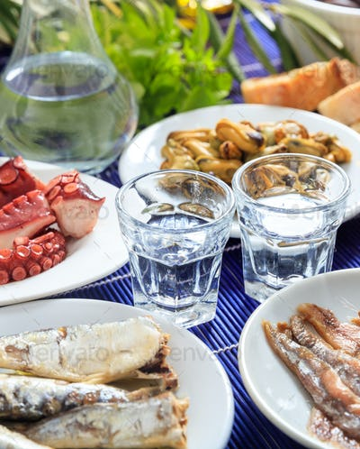 Ouzo, raki alcohol with seafood meze, vertical view