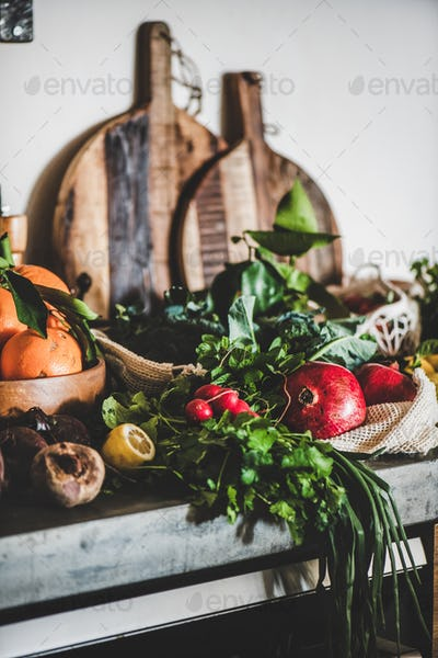 Fresh fruits, vegetables, nut, greens over grey concrete kitchen counter