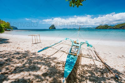 Holiday vibes. Traditional fishermen banca boat on sandy empty tropical beach. Blue ocean lagoon in