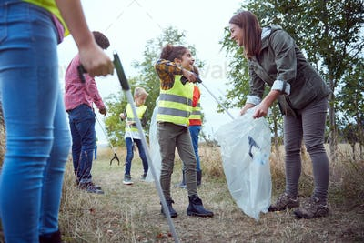 Adult Team Leaders With Group Of Children At Outdoor Activity Camp Collecting Litter Together