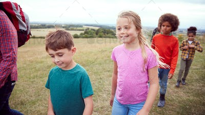 Adult Team Leaders With Group Of Children At Outdoor Activity Camp Walking Through Countryside