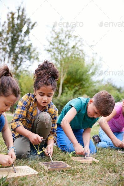 Group Of Children On Outdoor Camping Trip Learning How To Make Fire