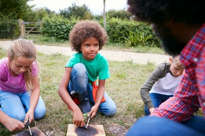 Team Leader Showing Group Of Children On Outdoor Camping Trip How To Make Fire