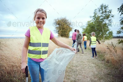 Portrait Of Girl With Adult Team Leaders At Outdoor Activity Camp Collecting Litter With Friends