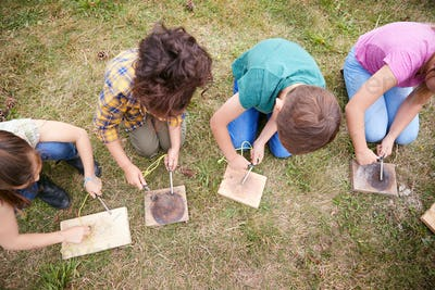 Overhead Shot Of Group Of Children On Outdoor Camping Trip Learning How To Make Fire