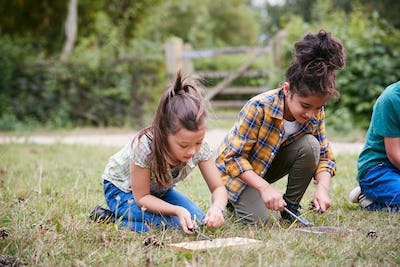 Two Girls On Outdoor Camping Trip Learning How To Make Fire