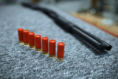 Rifle and row of ammo in gun shop, closeup, nobody