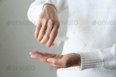 Female hands using hand sanitizer