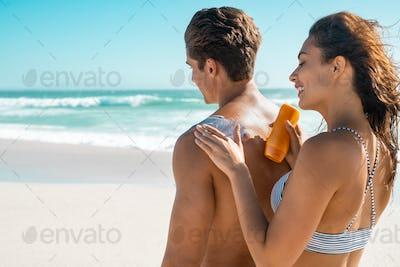 Woman applying sunscreen on man