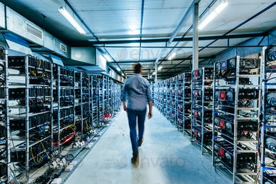 IT business owner walking in high tech data center full of servers and computers.