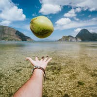 POV juggle with coconut in male hands against exotic islands in ocean bay