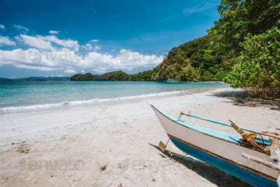 Traditional banca boat in front of remote tropical beach with exotic blue lagoon. El Nido