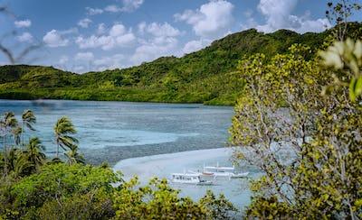 Beautiful view of a tropical Snake island. Sandbar and moored tourist boats. El Nido, Palawan