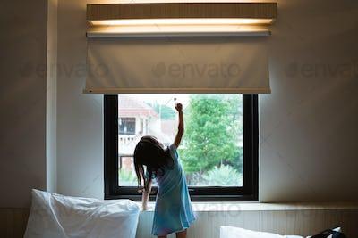 asian little girl reaching window curtain