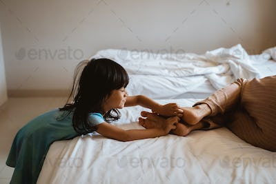little girl is tickling the feet of her mother