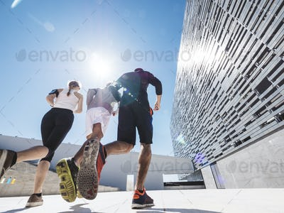 three friends athletes jogging in a modern building district