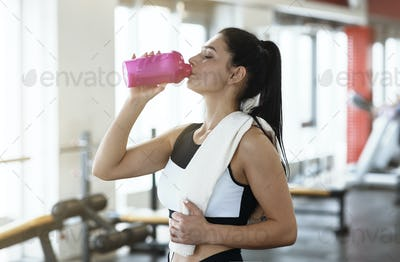 Keep hydrated. Young woman drinking water or protein cocktail in gym