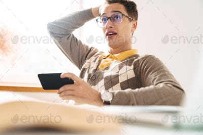 Shocked guy student sit at the table indoors using mobile phone.