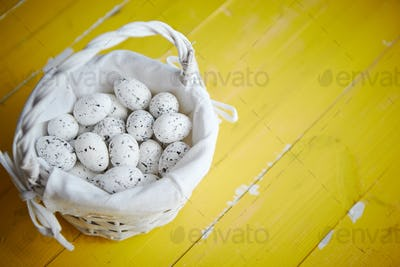 Quail eggs In white wicker basket. The concept of Easter Holidays