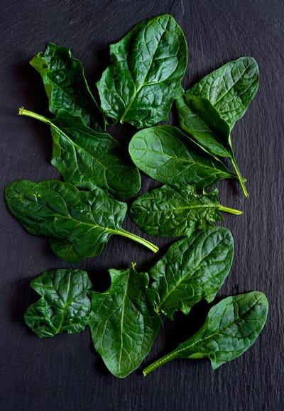 raw fresh spinach leaves on ardesia stone