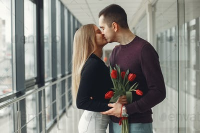 European couple is standing in a hall with a bunch of red tulips