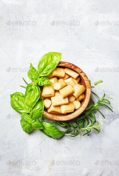 Smoked cheese in wooden bowl with green basil and rosemary