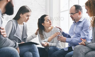 Concerned support group mebers comforting emotional young woman at therapy session