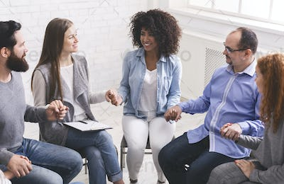Young multi-cultural group of people holding hands during therapy session