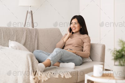 Relaxed girl chatting on phone, smiling and listening to call