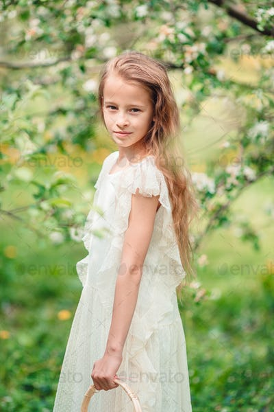 Adorable little girl in blooming apple garden on beautiful spring day