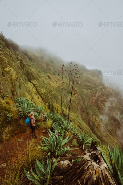 Female traveler staying on the cove volcano edge above the foggy green valley overgrown with agaves
