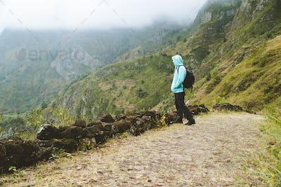 Active vacation tourism. Man enjoying impressive mountainscape. Arid canyon valley extend far below
