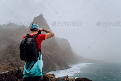 Male tourist with backpack on the scenic coastal road. The route leads along huge volcanic rock