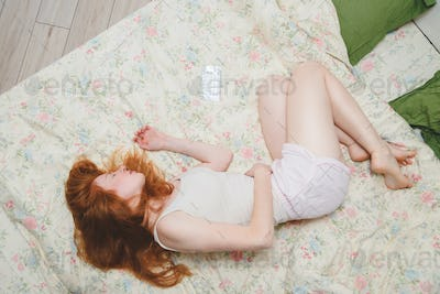 Young redhead woman suffering of stomach ache on bed. Top view. Keep her hands on underbelly.