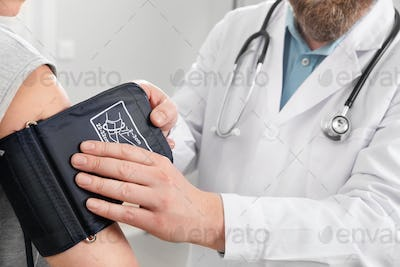 Doctor Checking Blood Pressure Of Patient In Hospital