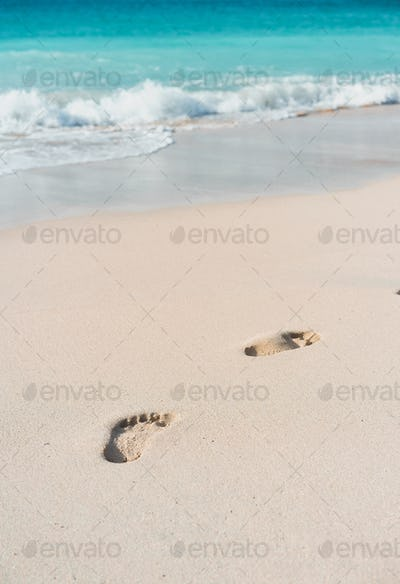 Azure ocean waves rolling on the beach with foot prints