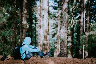 Traveler take a rest during hike in mysterious pine tree forest and endjoyed the silence. Santo