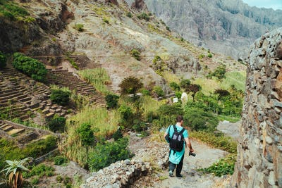 Santo Antao Cape Verde. Hiker with backpack going down the valley. Rocky terrain of high mountain