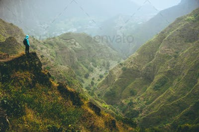 Male hiker on top of the mountain rock with gorgeous panorama view over high mountain ranges and