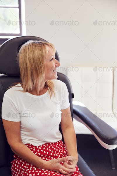 Mature Woman Sitting In Beauticians Chair Waiting For Botox Treatment