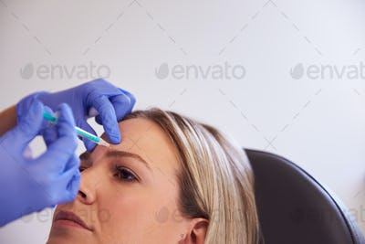 Woman Sitting In Chair Being Give Botox Injection In Forehead By Female Doctor