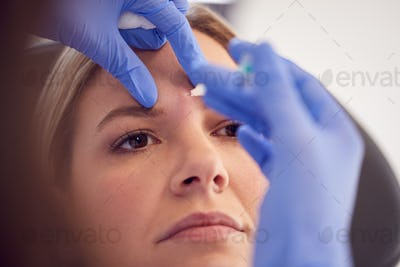Woman Sitting In Chair Being Give Botox Injection Between Eyes By Female Doctor