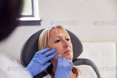 Mature Woman Sitting In Chair Being Give Botox Injection By Female Doctor