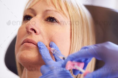 Close Up Of Mature Woman Sitting In Chair Being Give Botox Injection By Female Doctor