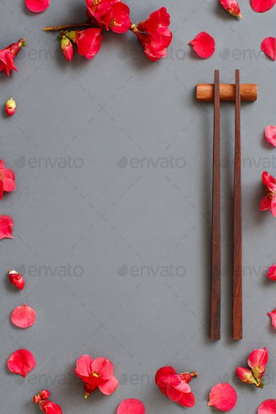 Chopsticks and pink flowers on gray background with copy space