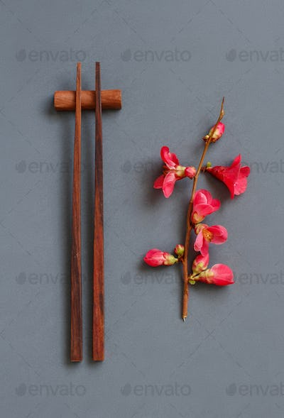Chopsticks and pink flowers on gray background