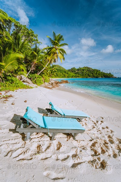 Mahe, Seychelles. Two sun lounger at beautiful Anse intendance beach. Blue ocean, white sand and