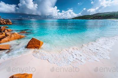 Gentle foam wave on Grand Anse beach, La Digue, Seychelles. White clouds, crystal clear ocean