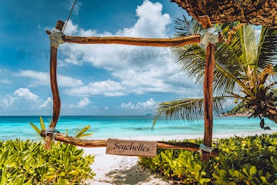 Tropical scene of bamboo frame at the white sand beach, turquoise ocean lagoon. Vacation in paradise